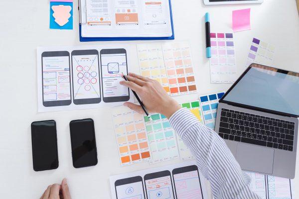 Creative ux designer designing screens for mobile responsive website development with UI/UX. Developing wireframe sketch layout design mockup on smartphone screen.